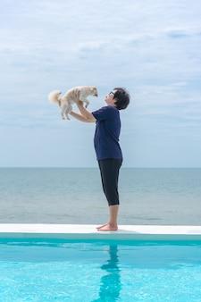 Asiatin und hund, die auf weißem strandbett am swimmingpool umarmen