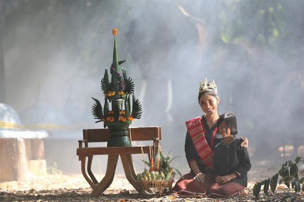 Asiatin und mädchen im gebürtigen traditionellen kostüm, das durch erntezeremoniesatz sitzt