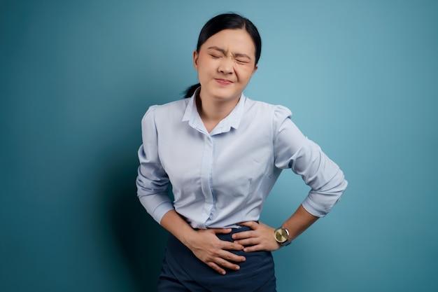 Asiatin war krank mit bauchschmerzen händchen haltend drückte ihren bauch