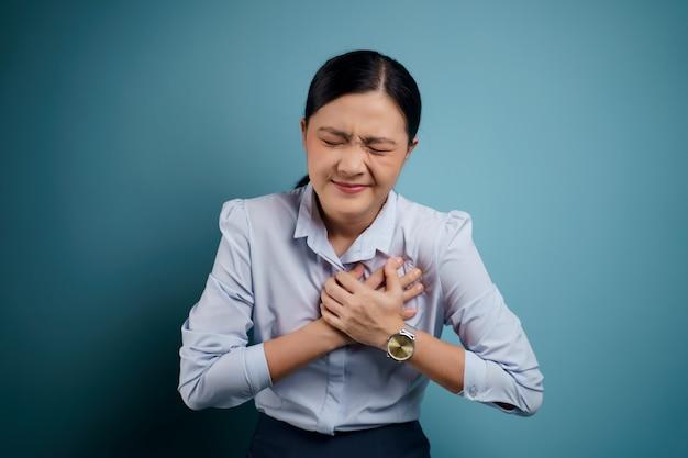 Asiatin war krank mit brustschmerzen, die isoliert auf blau standen.