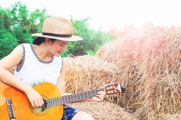 Asiatin, welche die gitarre sitzt auf stroh spielt. glückliche frau