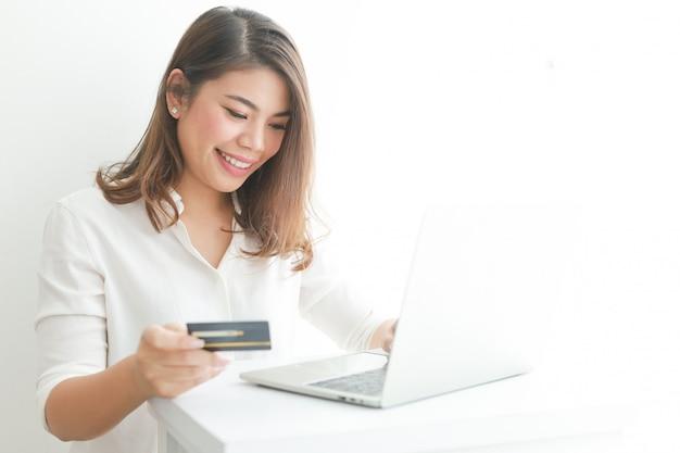 Asiatin, welche die kreditkarte online kauft mit laptop-computer verwendet,