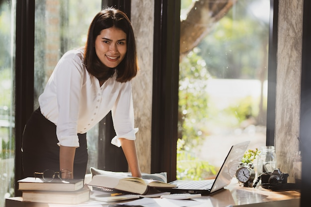 Asiatin, welche die laptop-computer arbeitet mit glücklichem verwendet.