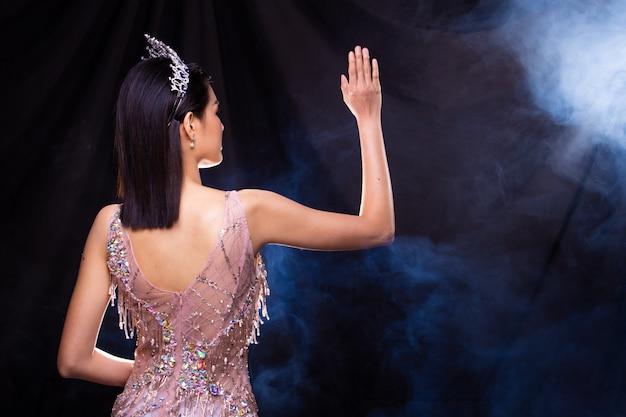 Asiatin zeigt wellenhand, um über dunkelheit mit seiten zu versehen