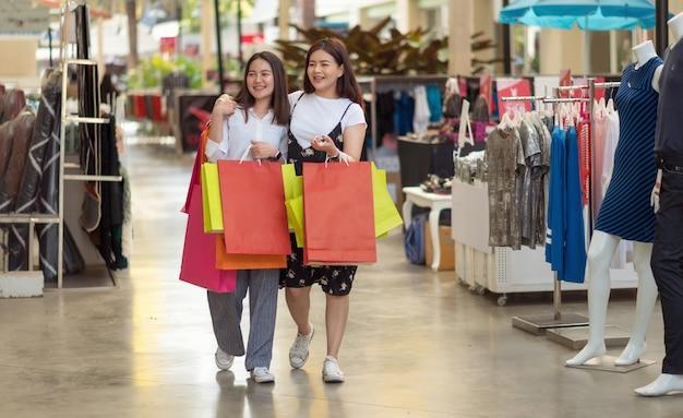 Asiatin zwei leute, die das einkaufen im einkaufszentrum genießen