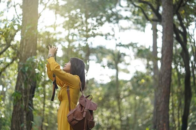 Asiatinabenteuer im wald und unter verwendung der kamera machen ein foto.