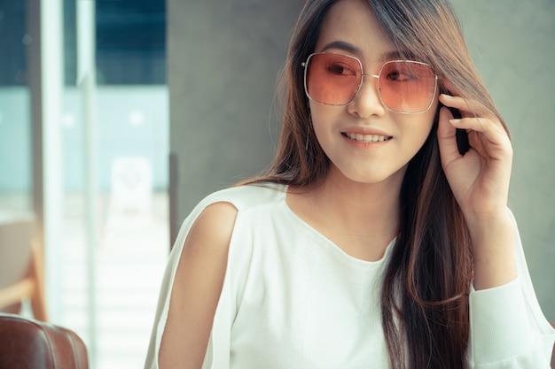 Asiatinabnutzungssonnenbrille und sitzen in einer kaffeestube.