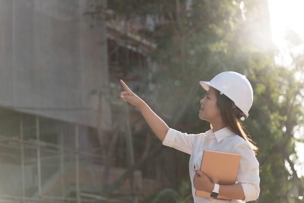 Asiatinbauingenieur mit weißer schutzhelmbesuchbaustelle.