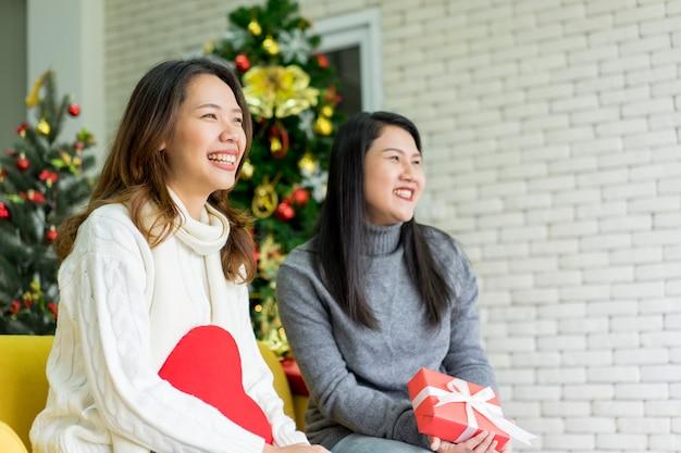 Asiatinfreunde sitzen auf couch und lachen zusammen im wohnzimmer für weihnachtsfeier