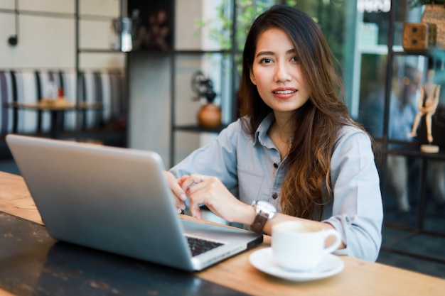 Asiatinfunktion und getränkkaffee im café mit laptop-computer lächeln und glücklicher arbeit