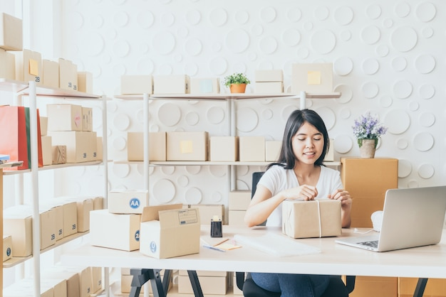 Asiatingeschäftseigentümer, der zu hause mit verpackungskasten auf arbeitsplatz arbeitet