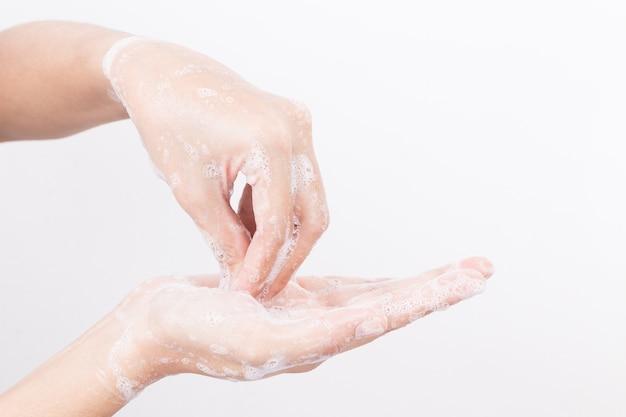 Asiatinhand waschen sich mit seifenblasen auf weißem hintergrund