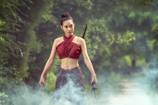 Asiatinkrieger in ayutthaya-kostüm, das im rauche steht.