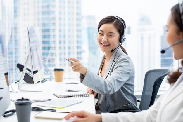 Asiatinkundendienstmitarbeiter, der im call-center-büro arbeitet