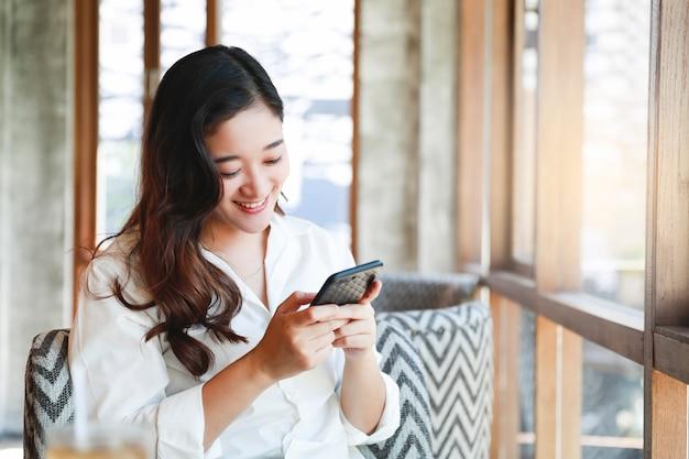 Asiatinlächeln mit dem handy, der im café sich entspannt