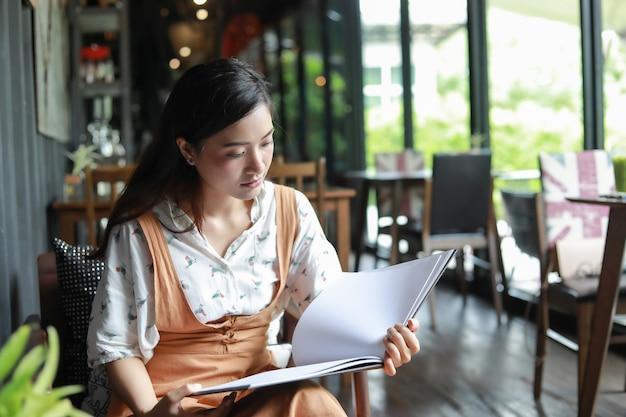 Asiatinlesebuch und lächeln und glückliche entspannung in einer kaffeestube