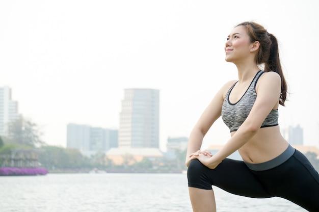 Asiatinleute wärmen für das laufen und yoga auf
