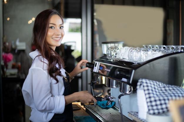 Asiatinnen barista, das kaffeemaschine im kaffeestubenzähler - kleinunternehmerlebensmittel- und -getränkcafé der berufstätigen frau lächelt und verwendet