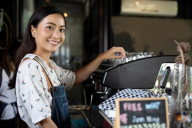 Asiatinnen barista, die kaffeemaschine im cafézähler lächeln und verwenden