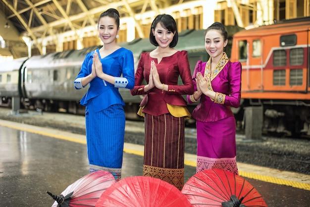 Asiatinnen begrüßen sawasdee mit traditionellem kostüm, reisekonzept