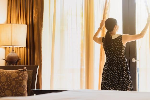 Asiatinnen bleiben in einem hotelzimmer. öffnen sie den vorhang im raum, der zur außenansicht schaut.