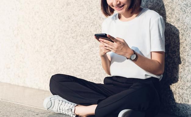 Asiatinnen des glücklichen lächelnden sitzens unter verwendung des smartphone.