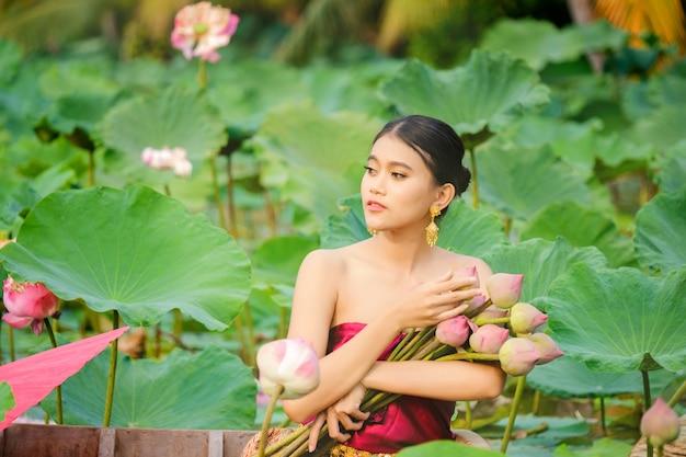 Asiatinnen, die auf hölzernen booten sitzen, um lotos zu sammeln