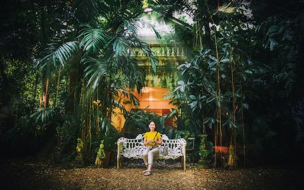 Asiatinnen, die auf weißem benchmark im naturgrünpark-weinleseton sitzen