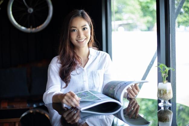 Asiatinnen, die ein buch für entspannung am kaffeecafé lächeln und lesen