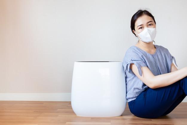 Asiatinnen, die ein gesundheitsproblem von der luftverschmutzung in ihrem haus hat, das neben der luftreinigermaschine im wohnzimmer auf dem bretterboden sitzt