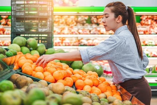 Asiatinnen, die gesundes lebensmittelgemüse und -früchte im supermarkt kaufen