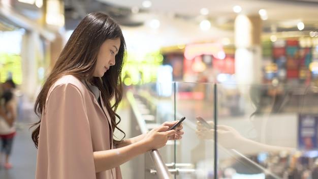 Asiatinnen, die handys in den einkaufszentren spielen