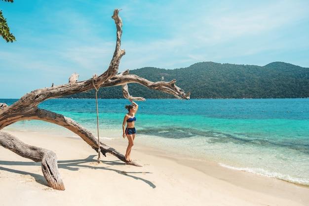 Asiatinnen, die in den sommerferien auf strand sich entspannen