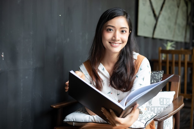 Asiatinnen, die in einer kaffeestube lesen und lächeln und glücklich sich entspannen, nachdem in einem erfolgreichen büro gearbeitet worden ist.