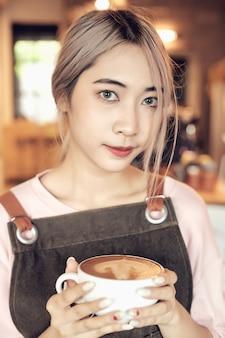 Asiatinnen, die kaffeetasse am café halten