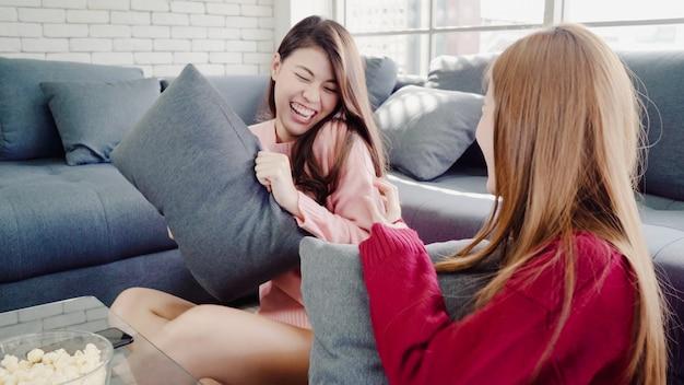 Asiatinnen, die kissenschlacht spielen und zu hause popcorn im wohnzimmer, gruppe des mitbewohners essen