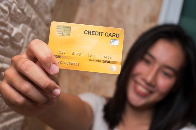 Asiatinnen, die kreditkarte zeigen