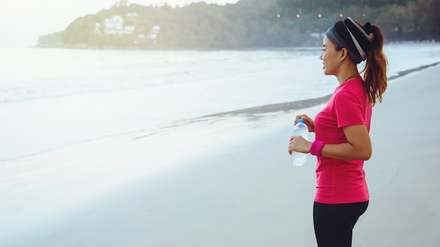 Asiatinnen, die morgens training auf dem strand rütteln.