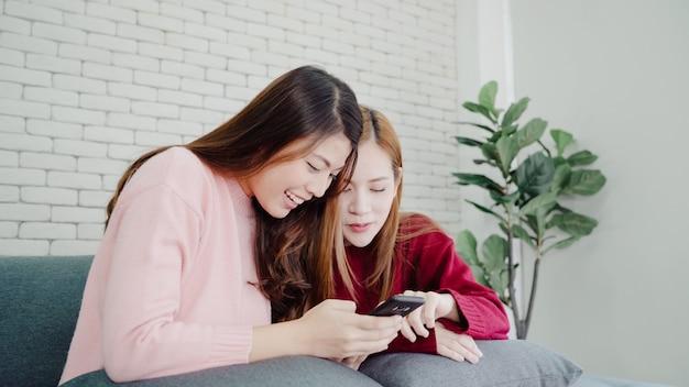 Asiatinnen, die smartphone verwenden social media im wohnzimmer zu hause, gruppe des mitbewohners überprüfen