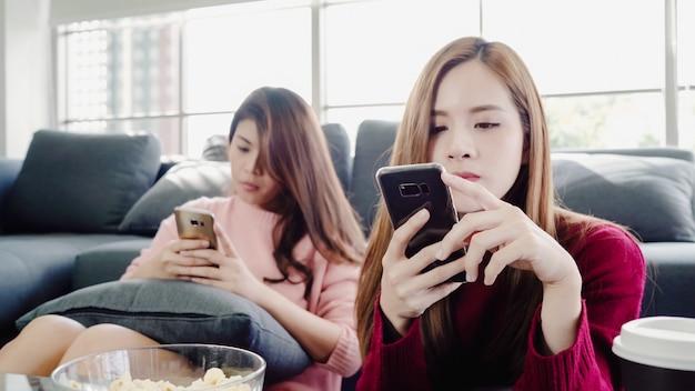 Asiatinnen, die smartphone verwenden und zu hause popcorn im wohnzimmer, gruppe des mitbewohners essen