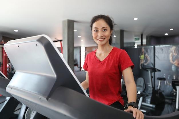 Asiatinnen, die sportschuhe an der turnhalle laufen lassen und auf der tretmühle rütteln lassen
