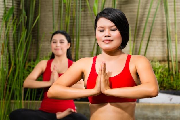 Asiatinnen, die yoga in der tropischen einstellung tun