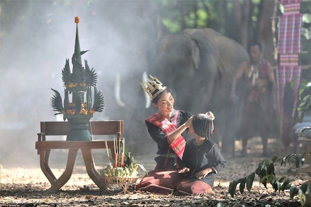 Asiatinnen im gebürtigen traditionellen kostüm, das durch erntezeremonie sitzt, stellten auf tabelle gegen elefanten ein.