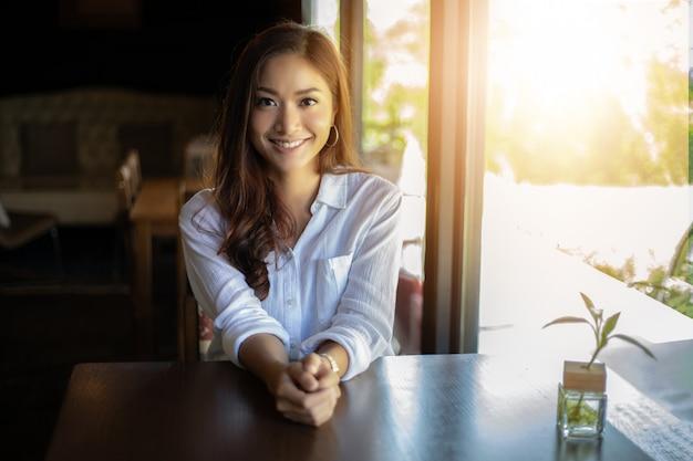 Asiatinnen lächelnd und glücklich, entspannend in einer kaffeestube