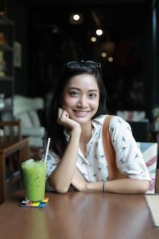 Asiatinnen lächelnd und glücklich, entspannend mit grünem tee in einer kaffeestube
