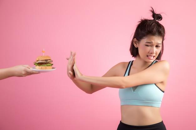 Asiatinnen lehnen schnellimbiß wegen des abnehmens auf rosa ab