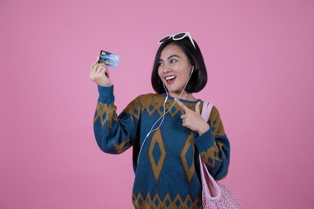Asiatinnen mit der sonnenbrille, rosa tasche und kopfhörer, die kreditkarten zeigen.