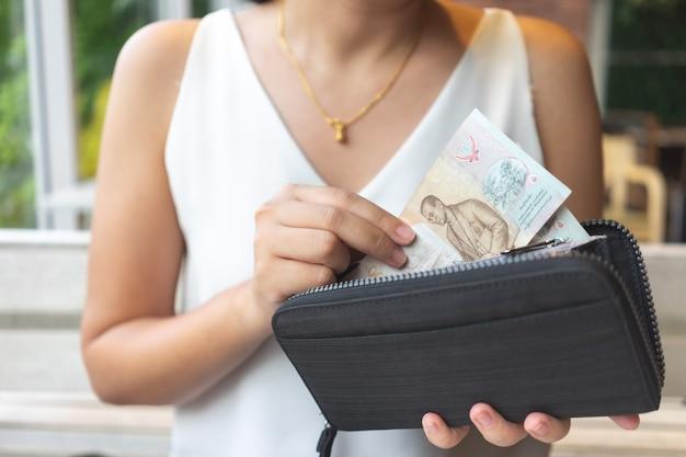 Asiatinnen nehmen thailändische banknoten aus der handtasche, um für lebensmittel oder dienstleistungen zu bezahlen.