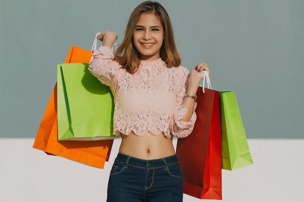 Asiatinnen schönes mädchen hält einkaufstaschen und lächelt