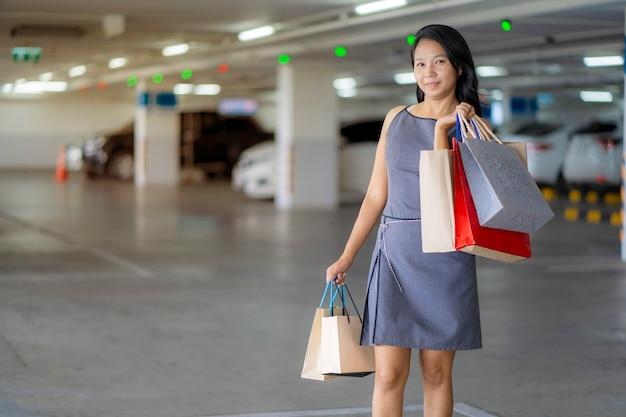 Asiatinnen sind glückliches einkaufen an den kaufhäusern, einkaufstaschen